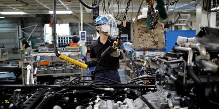 An employee wearing a protective face mask and face guard works on the automobile assembly line during the outbreak of the coronavirus disease (COVID-19) at the factory of Mitsubishi Fuso Truck and Bus Corp. in Kawasaki