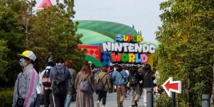 Visitors walk toward to Super Nintendo World at the Universal Studios Japan theme park in Osaka, Japan