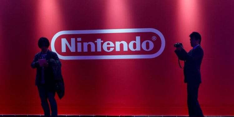 FILE PHOTO: People stand in front of Nintendo's logo at the presentation ceremony of its new game console Switch in Tokyo