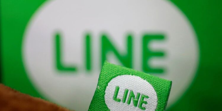 FILE PHOTO: The logo of free messaging app Line is pictured on a smartphone and the company's stuffed toy in this photo illustration taken in Tokyo
